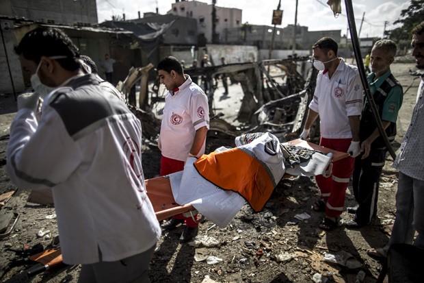 Palestinos carregam o corpo carbonizado de um motorista de ambulância, morto na noite de sexta-feira em Beit Hanun, na Faixa de Gaza (Foto: AFP Photo/Marco Longari)