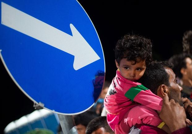 Refugiados fazem fila enquanto esperam ônibus em Heiligenkreuz, na fronteira entre Áustria e Hungria, no fim da noite desta terça-feira (15) (Foto: Christian Bruna/AP)