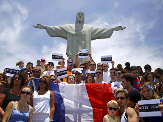 Pessoas se reúnem com cartazes e bandeira da França em frente ao Cristo Redentor, no Rio de Janeiro, para prestar solidariedade após os ataques terroristas em Paris (Foto: Pilar Olivares/Reuters)