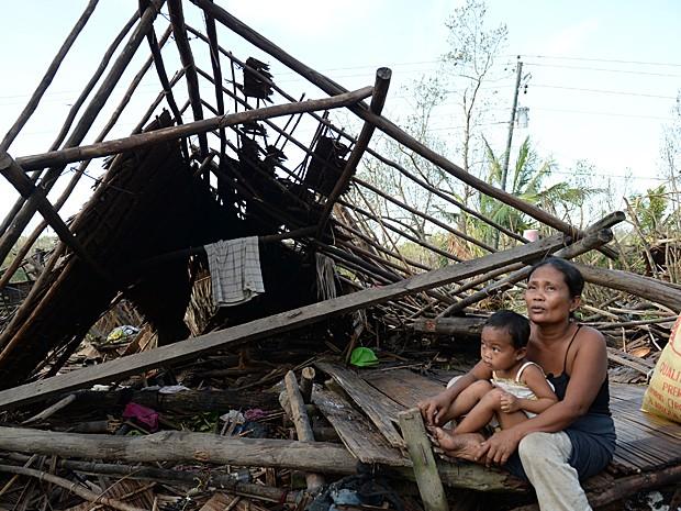 Mãe e filho sentados sob os escombros da casa da família que foi destruída na ilha de Samar, uma das mais atingidas pelo tufão nas Filipinas (Foto: Ted Aljibe/AFP)