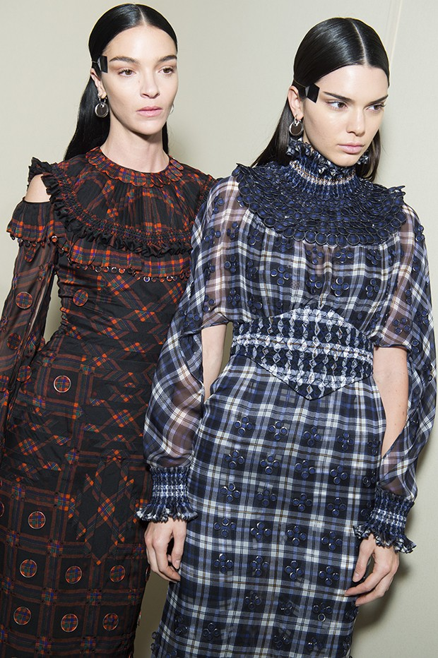 Mariacarla Boscono (left) wears a Givenchy Haute Couture silk chiffon tartan-print dress with hand-pleated neck, cuffs, and hem; embellished with thin chiffon-covered metal disks. Matched with a printed jersey lace-encrusted jumpsuit. Kendall Jenner wears a silk-chiffon tartan-print dress with hand-smocked neck, waist, and wrists; embellished all over with small, graduated metal, chiffon-covered disks worn with a printed jersey lace-encrusted jumpsuit. (Foto: Givenchy)