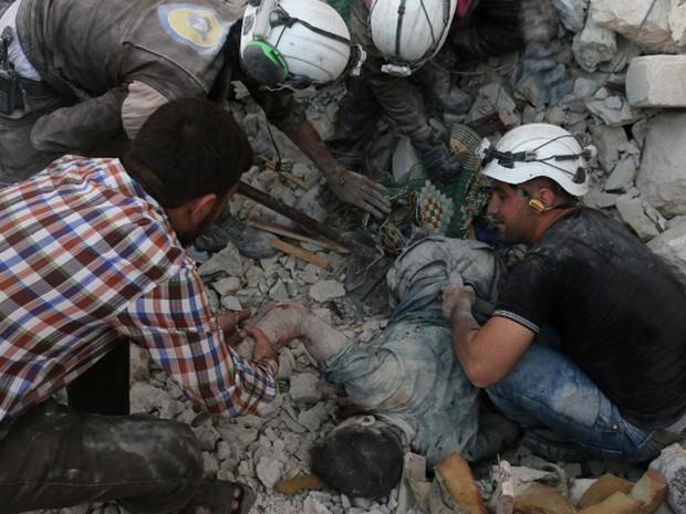 Voluntários da defesa civil retiram corpo de homem dos destroços após ataques aéreos que destruíram imóveis no norte de Aleppo, na Síria, na quarta-feira (27) (Foto: Ameer Alhalbi / AFP)