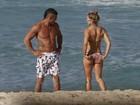 Joana Prado exibe curvas em praia carioca e Vítor Belfort admira a mulher