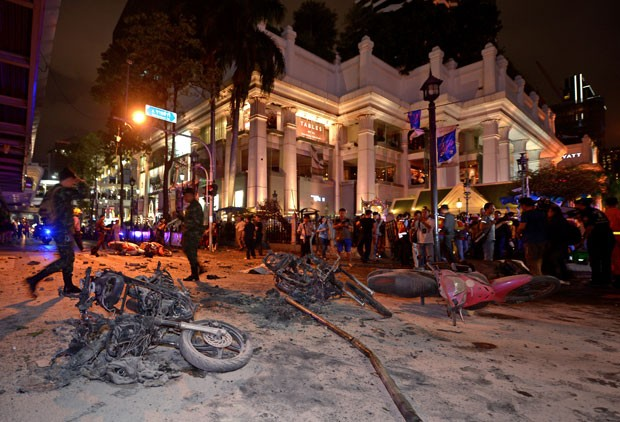 Policiais e moradores olham para região onde explodiu uma bomba no centro de Bangcoc (Foto: Pornchai Kittiwongsakul / AFP)