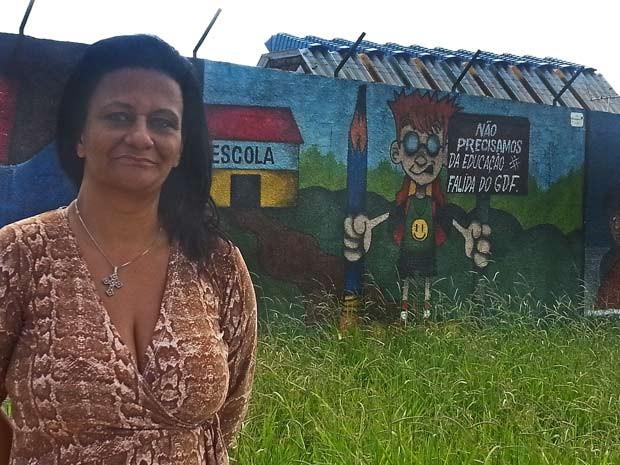 A diretora do Caic Unesco, Heloisa Moraes; ao fundo, o grafite que critica a educação do DF (Foto: Raquel Morais/G1)