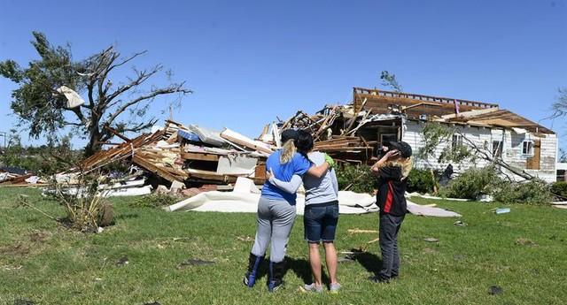 Irmãos observam o que restou da casa da família em El Reno, em Oklahoma, Estados Unidos (Foto: EFE/EPA/LARRY W. SMITH)