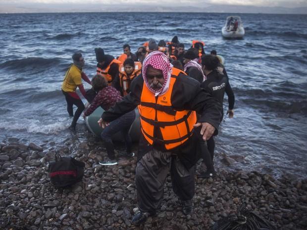 Iraquiano desembarca de um bote após cruzar o mar da costa da Turquia até uma praia de Lesbos, ilha da Grécia, com outros refugiados e migrantes. Milhares de pessoas seguem chegando à Europa, em fuga dos conflitos no oriente Médio (Foto: Santo Palacios/AP)