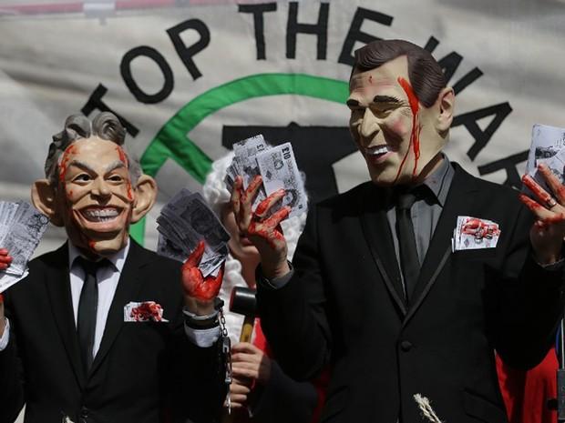 Manifestantes usam máscaras de Tony Blair e George W. Bush, em protesto contra a invasão do Iraque em 2006, que acontece em Londres, nesta quarta-feira (6)  (Foto: Daniel Leal-Olivas / AFP)