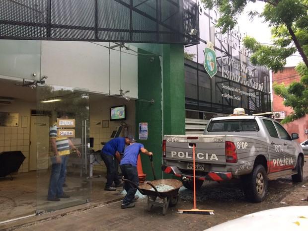 Fachada do 8º DP foi atingida e policiais recolhem vidro na manhã desta sexta-feira (22) (Foto: Wânyffer Monteiro/TV Verdes Mares)