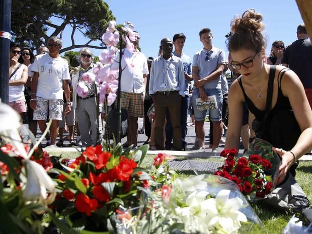 Uma mulher coloca um buquê de flores perto do local onde um caminhão atropelou multidão em Nice (Foto: REUTERS/Pascal Rossignol)