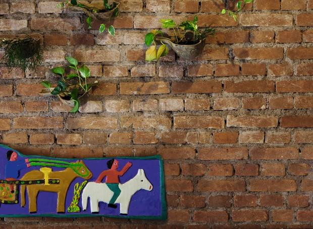 A escultura feita em madeira de artista alagoano alegra a parede do salão, onde o chef volta e meia surge, vindo da cozinha, para circular entre as mesas (Foto: Lufe Gomes)