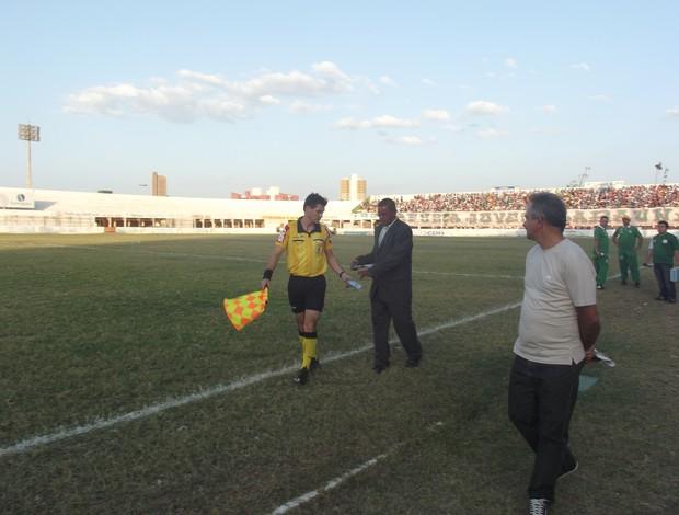 Bandeira entrega garrafa plástica a delegado da partida em jogo entre Baraúnas e Campinense (Foto: Bruno Araújo/Globoesporte.com)