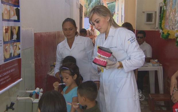 Dentistas ensiando as criabças a maneira correta de escovar os dentes na Ação de saúde no bairro Perpétuo Socorro (Foto: Reprodução/TV Amapá)