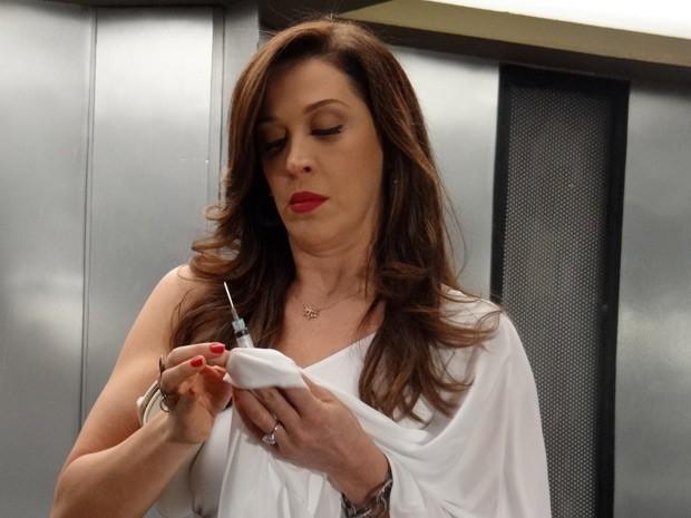 Lívia tira suas impressões digitais da seringa  (Foto: Salve Jorge/TV Globo)
