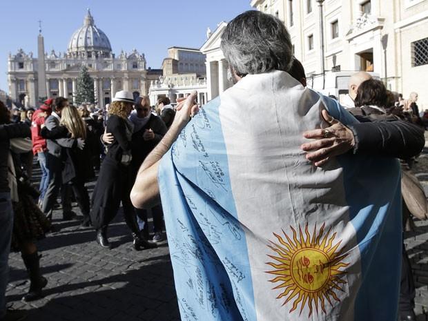Fieis com a bandeira da Argentina dançam tango na Praça São Pedro (Foto: Alessandra Tarantino/AP)