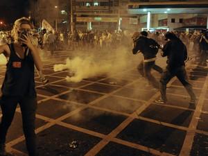 Pessoas fogem de bombas lançadas por policiais no Rio de Janeiro (Foto: Tasso Marcelo/AFP)