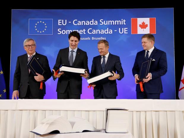 Presidente da Comissão Europeia, Jean-Claude Juncker, premiê canadense Justin Trudeau, presidente do Conselho da União Europeia, Donald Tusk, e premiê da Eslováquia, Robert Fico, durante a cerimônia de assinatura do Ceta em Bruxelas (Foto: Francois Lenoir/ Reuters)