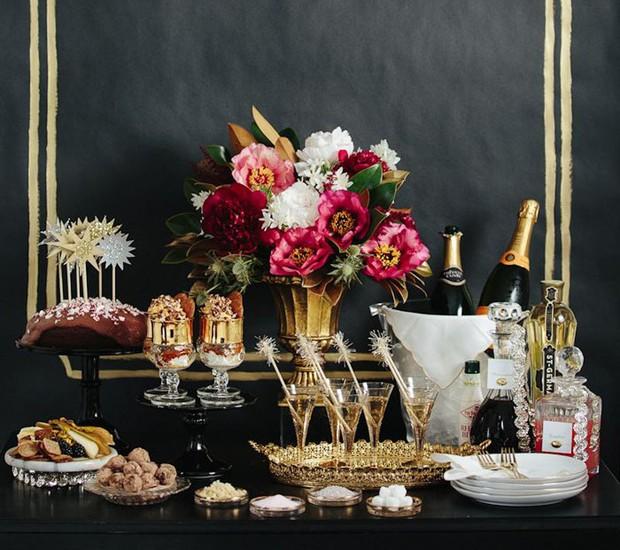 Ótima ideia para as festas de fim de ano: um fundo preto e cores elegantes, como o dourado e branco, dão sofisticação à estação de bebidas. Complete o decór com um lindo arranjo de flores.  (Foto: Reprodução/Pinterest)