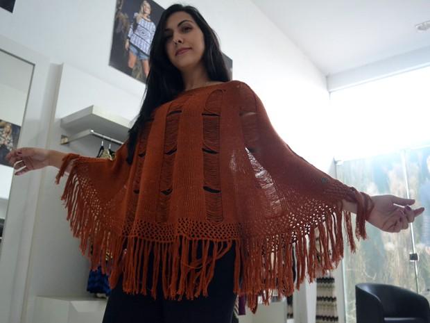 Entre as estrelas da estação, o poncho volta em versão mais despojada ao guarda-roupa; na imagem, Janaína Soléo mostra modelo de sua coleção em Jacutinga, MG (Foto: Daniela Ayres/ G1)