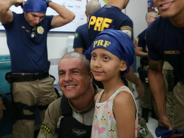 Mariana ganhou bandana, uma boneca e tirou muitas fotos durante a visita dos policiais no Hospital do Câncer (Foto: Nathália Lorentz/G1)
