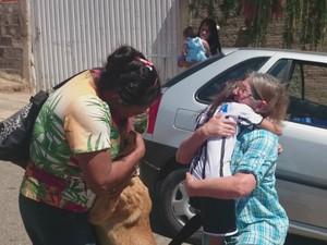 Lindinalva abraça a cachorra enquanto vizinha se emociona ao ver a criança  (Foto: Gláucia Souza / G1)