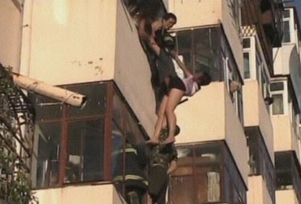 Mulher é vista pendurada em prédio em Heilongjiang, na China (Foto: CCTV/Reuters)