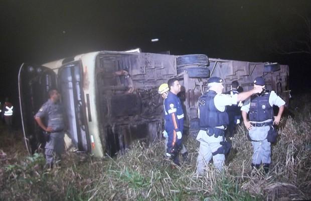 Policiais prestam atendimento no local onde ônibus capotou em Luziânia (Foto: Reprodução / TV Globo)