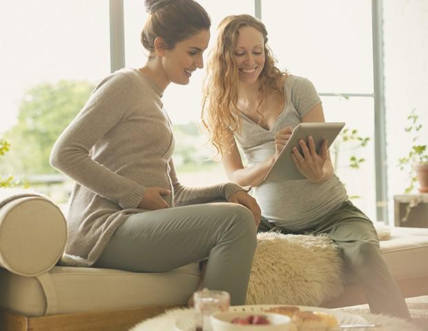 Duas mulheres grávidas conversando com o ipad na mão (Foto: Caiaimage/Tom Merton/getty images)