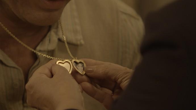 Anastácia vê o medalhão no peito de Ernesto (Foto: TV Globo)