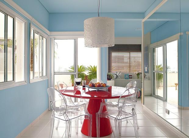 Na sala de jantar decorada pela arquiteta Andrea Murao, o azul predomina nas paredes. A mesa vermelha faz o contraponto (Foto: Victor Affaro/Editora Globo)