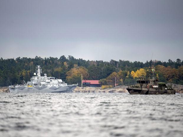 O navio sueco rastreador de minas HMS Kullen e um barco da guarda costeira navegam nesta terça (21) na Baía de Namdo, no quinto dia de buscas por um suposto minissubmarino russo na região de Estocolmo (Foto: AFP Photo/TT News Agency/Fredrik Sandberg)