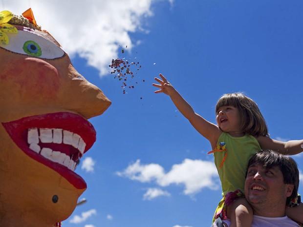 Menina joga confete em boneco no carnaval de São Luiz do Paraitinga. retratos* (Foto: Roosevelt Cassio / Reuters)