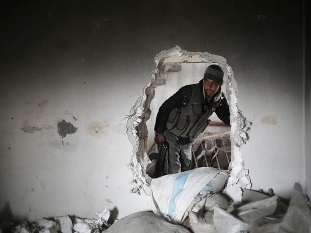 Combatente rebelde anda em uma construção semidestruída em Damasco  (Foto: Amer Almohibany / AFP)