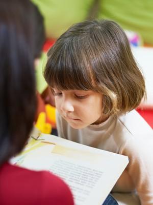 Professora lendo livro para criança (Foto: Shutterstock)