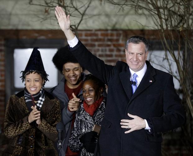 Ao lado da família, Bill de Blasio acena após prestar juramento nesta quarta-feira (1º) como prefeito de Nova York (Foto: Seth Wenig/AP)