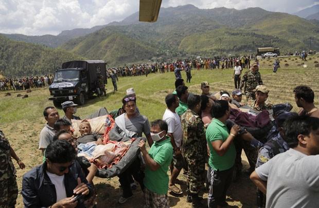Feridos em terremoto são retirados por helicópteros indianos nesta segunda-feira (27) em Katmandu (Foto: Altaf Qadri/AP)