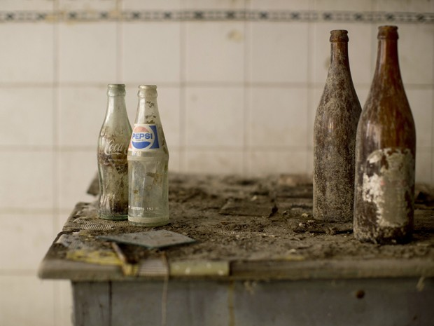 Garrafas abandonadas no balcão de um café que fica na zona 'proibida' da linha que divide o Chipre desde 1974 (Foto: Neil Hall/Reuters)