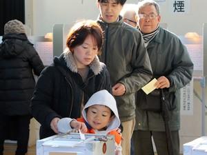 Menino ajuda a mãe a depositar voto em Tóquio, neste domingo (14)  (Foto: AFP Photo/Yoshikazu Tsuno)