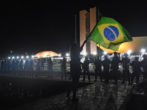 Pessoa sacode bandeira do Brasil diante de barreira policial em frente ao Congresso Nacional, em Brasília (Foto: Evaristo Sá/AFP)