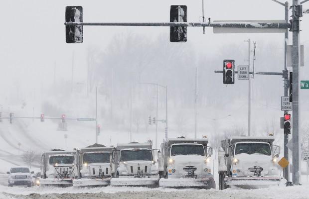 Escavadeiras para retirada de neve aguardam em semáforo nos EUA (Foto: Orlin Wagner/AP)