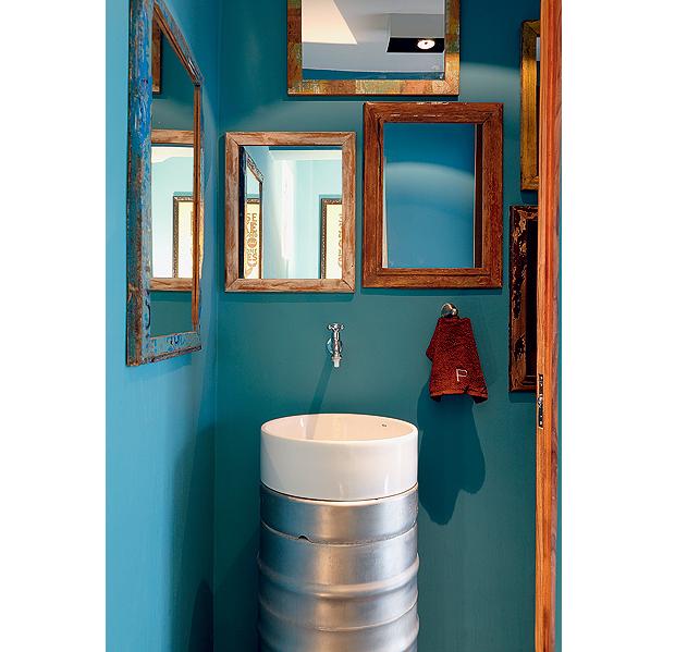 Neste lavabo inusitado, a pia foi feita com dois barris de chope e uma cuba. Ligada direto à parede, a torneira de jardim dá um ar rústico ao espaço, que tem espelhos com moldura de madeira de demolição. Nas paredes, cor turquesa. Projeto da arquiteta Luc (Foto: Evelyn Müller/Casa e Jardim)