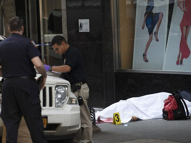 Detetives da Polícia de Nova York examinam local ao lado do corpo de suposto atirador que abriu fogo contra transeuntes em frente ao edifício Empire State Building, em Nova York.  (Foto: Keith Bedford/Reuters)