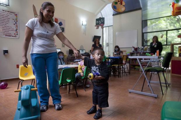Jesús brinca ao lado de sua mãe, María Fernández, no Centro Médico de La Raza, na Cidade do México (Foto: Esteban Felix/AP)