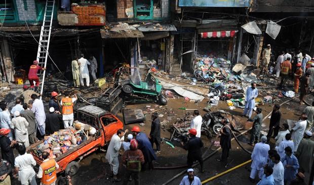Autoridades de segurança do Paquistão e voluntários se reúnem no no movimentado mercado em Peshawar Kissa Khwani, local da explosão de uma bomba neste domingo (29).  (Foto: A. Majeed/AFP)
