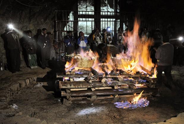 """Mineiros assistem fogo durante o """"Wilancha"""", o rital de sacrifício de animais, dentro de uma mina de estanho  de Nueva San Jose, próximo a Oruro, na Bolívia, nesta sexta-feira (8) (Foto: Aizar Raldes/AFP)"""