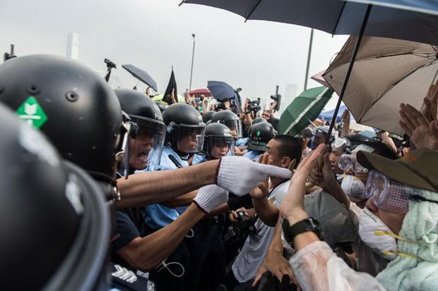 Policiais formam barreira para ambulância passar por manifestantes em frente à sede do governo de Hong Kong nesta sexta-feira (3) (Foto: Anthony Wallace/AFP)