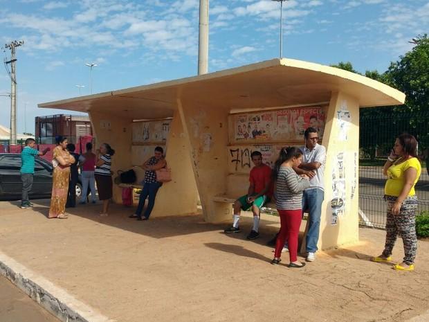 Funcinários do Campus que não puderam entrar aguardam em parada de ônibus em frente à UnB de Planatina (Foto: Elielton Lopes/G1)