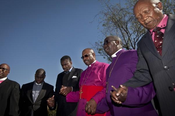 Bispos rezam pela recuperação do ex-presidente da África do Sul Nelson Mandela, perto do hospital onde está internado, em Pretória. Mandela luta contra uma grave infecção pulmonar  (Foto: AP Photo/Ben Curtis)