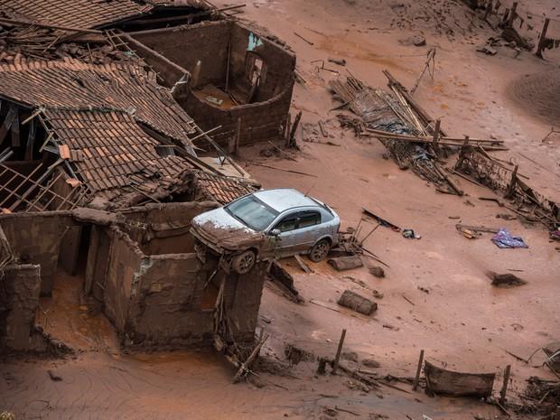 06/11 - Um carro é visto sobre os destroços de uma casa em meio a lama após o rompimento de uma barragem de rejeitos da mineradora Samarco no Distrito de Bento Rodrigues, no interior de Minas Gerais (Foto: Christophe Simon/AFP)