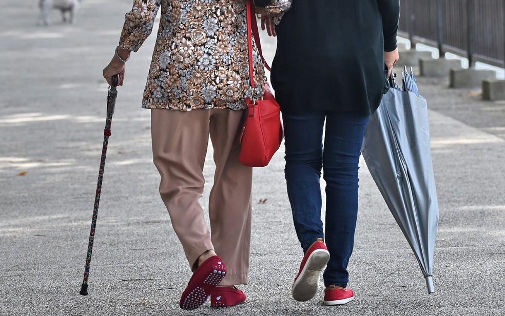 Idosa caminha ao lado de cuidadora em parque em Cingapura (Foto: Roslan Rahman/AFP)